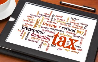 cloud  of words related to taxes, preparation, paying, income, refunds, on a digital tablet with a cup of tea